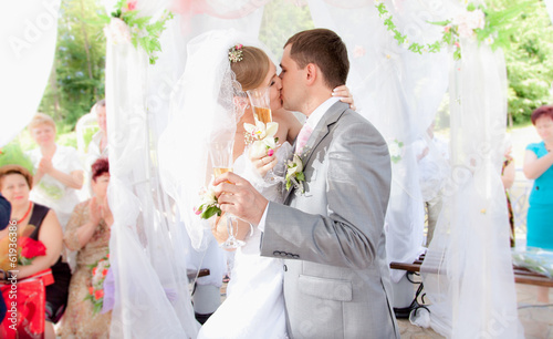 Closeup portrait of just married couple kissing during ceremony
