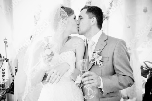 closeup portrait of bride and groom kissing at alcove