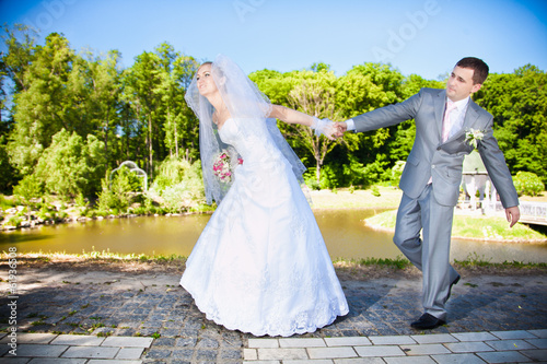 Beautiful bride holding grooms hand and leading him