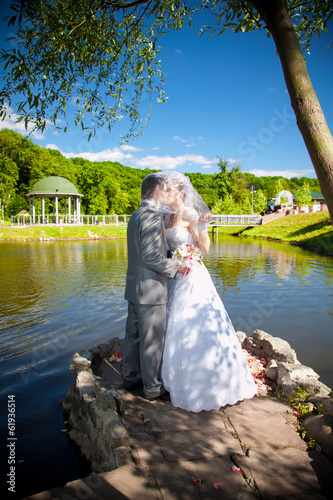 Young bride and groom kissing on river bank at park