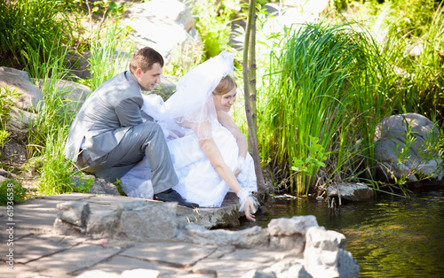 Newly married couple sitting on riverbank and touching water