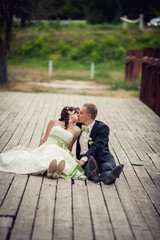 wedding. Beautiful newly married couple kissing on a bridge