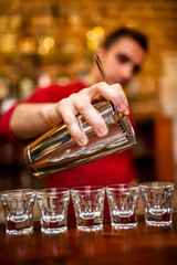 Close-up of Barman pouring alcoholic drink and cocktails