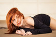 Sensual young red head woman portrait while lying on bed in hote