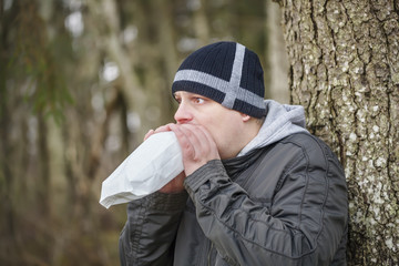 Worried man breathe into a paper bag near tree