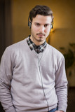 Attractive young man listening to music on headphones at home