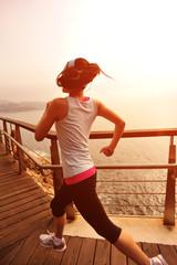 fitness  young woman running seaside wooden bridge