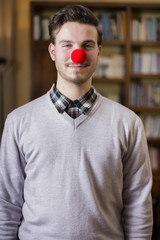 Handsome young man smiling with red clown nose