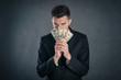 Man hiding behind dollars banknotes with furtive expression agai