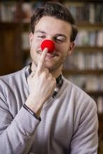 Przystojny młody mężczyzna uśmiecha się i dotykania czerwony nos klauna