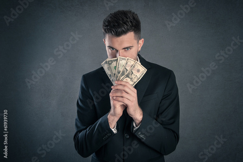 Man hiding behind dollars banknotes with furtive expression agai