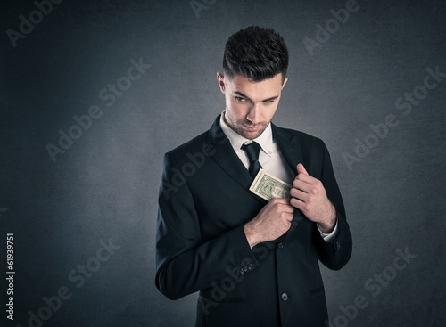 Man taking dollars banknotes with stealthy expression against gr