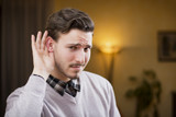 Handsome young man can't hear, putting hand around his ear