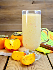 Milkshake with persimmons in goblet on board