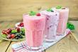 Leinwandbild Motiv Milkshakes with berries in glass on board