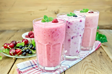 Milkshakes with berries in glass on board