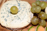 Cheese with white grapes . Close up