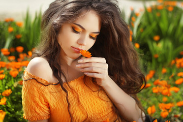 Beautiful Teenage Model girl smelling flower, over marigold flow