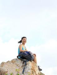 woman hiker sit seaside mountain peak rock