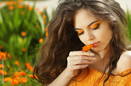 Outdoors portrait of Beautiful Teen girl smelling flower, over m