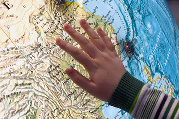 Child's hand on the big globe