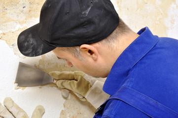 Handwerker kratzt Tapete von Wand