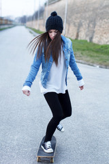 Young brunette skateboarder girl practice