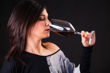 Wine expert tasting wine. Black background.