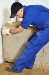 Handwerker entfernt alten Teppich