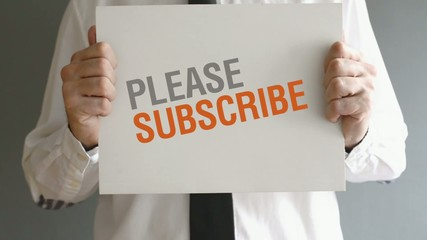 Businessman holding paper with Please subscribe title. Business