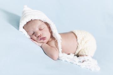 Newborn kleiner Bub schlafend mit weißer Mütze
