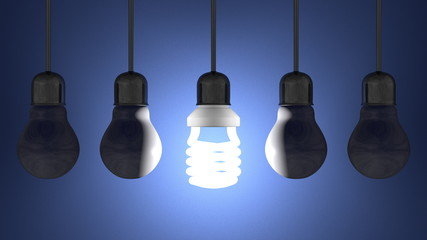 Glowing spiral light bulb, dead tungsten ones hanging on blue