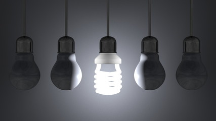 Glowing spiral light bulb, dead tungsten ones hanging on gray