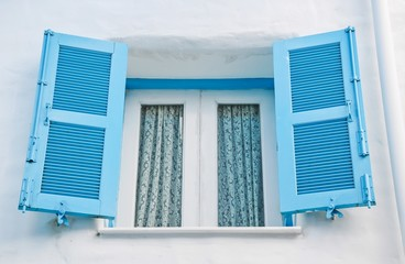 Greek Style windows with blue retro wooden shutters on white wal