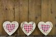 Drei karierte rote Herzen auf Holz als Grußkarte ländlich
