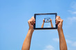 hands holding tablet in blue sky