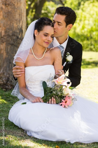 Groom kissing his beautiful bride at park