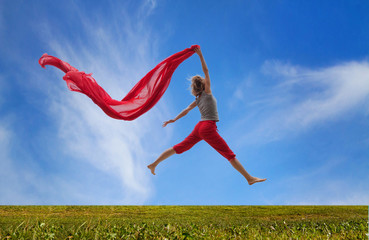 happy girl jumping with red fabric