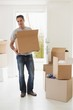 Smiling man carrying boxes in new house