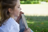 Close-up of young girl reading book in park