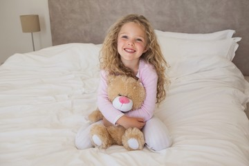 Young happy girl with stuffed toy sitting on bed