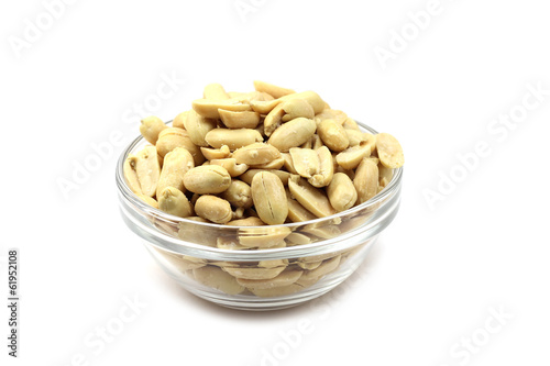 Salted peanuts in a glass container on white background