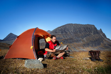 Hiker in front of his Tent, looking Map