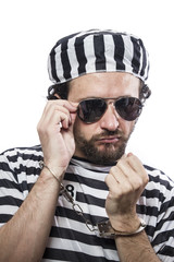 Desperate, portrait of a man prisoner in prison garb, over white