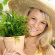 Gärtnerin mit Topfpflanze lächelt