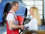 Female customer and mechanic shake hands
