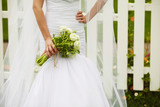 Bride's hands with wedding bouquet over white fence