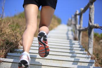 runner legs running at mountain stone stairs