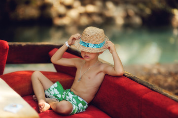 Outdoors on a red couch resting fun boy in a hat