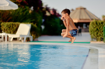 hot summer day, the boy dives and swims in the pool with turquoi